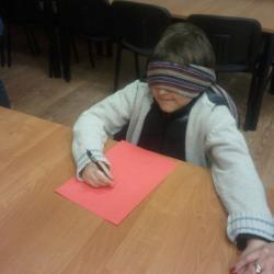 Łukasz na zabawie karnawałowej z Opolnicy rysuje, ale jego ręka wędruje w górę do odsłaniania oczu, więc Pani przytrzymuje rękę .