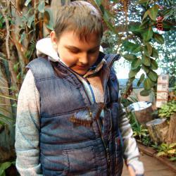 Łukasz patrzy zainteresowaniem na motylka, który usiadł na jego kamizelce.